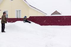 A little boy riding on a snowy hill Stock Photos