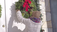 Teen Helps Decorate Family Home, She Hangs A Christmas Wreath, And Smiles Stock Footage