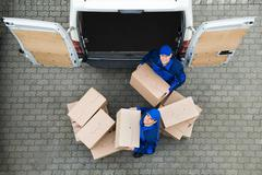 Directly above portrait of delivery men carrying cardboard boxes outside truc Stock Photos