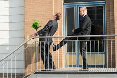 Stock Photo of Side view of businessman kicking employee carrying box with belongings outsid