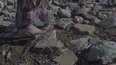 Close up detail of a woman's feet in a long dress standing on big stones with Stock Footage