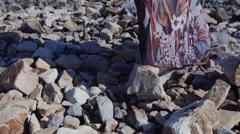 Close up detail of a woman's feet in a long dress standing on big stones Stock Footage