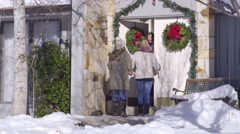 Girls Carry Christmas Gifts, Friend Opens Door And Invites Them Inside Stock Footage