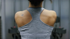 Back of a weightlifter as she pulls weights from a machine Stock Footage