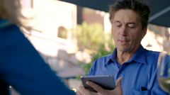 Middle-aged man smiles as he uses his tablet at a restaurant - stock footage