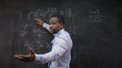 4K Young teacher writing math formula on blackboard & addressing students Stock Footage