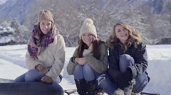 Teens Sit On Their Sleds And Smile, Girl Laughs At Someone Off-Screen Stock Footage