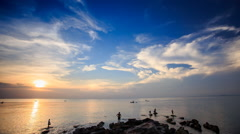 Silhouettes in Sea by Rocks Boats Sun from Behind Clouds - stock footage