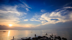Motion from Silhouettes in Sea to Sun behind Clouds at Sunset - stock footage