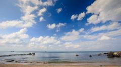 Sea Bay with Wooden Pier Rocks Waves Splash against Sky Stock Footage