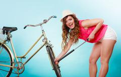 Stock Photo of Happy woman pumping up tire tyre with bike pump.