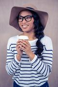 Attractive Asian woman with hat holding disposable cup - stock photo