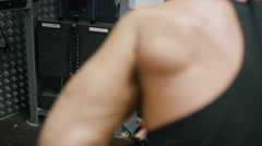 Focus pull from weights to the back of a muscular body builder, in slow motion Stock Footage