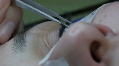 Eyelash extensions. beautician glues lashes with tweezers, extreme close up. Stock Footage
