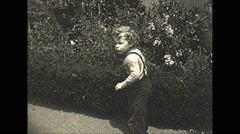 Vintage 16mm film, 1945 USA, toddler looking for something lost Stock Footage
