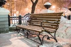 Bench in winter city park - stock photo