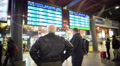 Two male passengers waiting for a train, checking timetable on display screen Footage