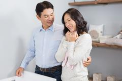 Happy couple holding pink onesie - stock photo