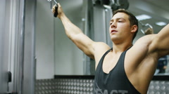 Handsome muscular young man working out on a cable machine, in slow motion Stock Footage