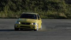 Yellow car screeching around a corner at drifting event. Stock Footage