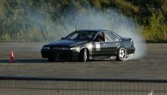 Nissan Maxima drifts around corners in slow motion at drifting event. Stock Footage