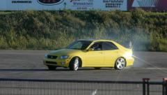 Yellow car does a huge drift around corner at drifting event. Stock Footage