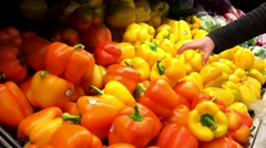 Woman selecting yellow pepper in grocery store produce department Stock Footage