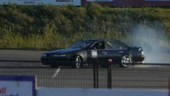Nissan Maxima drifting around corner on closed course at drift practice event. Stock Footage