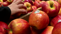 Woman selecting red apple in grocery store produce department Stock Footage