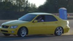 Yellow car drifts around corner at drifting event on closed course. Stock Footage