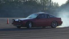 Red car screeches around corner at drifting race event. Stock Footage
