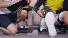 4K Disabled athlete at the gym puts on prosthetic leg to prepare for workout - stock footage