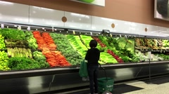 Woman buying green onion in grocery store produce department - stock footage