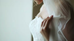 Beautiful bride standing at the window Stock Footage