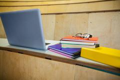 Students books and laptop in an auditorium - stock photo