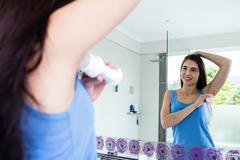 Smiling brunette putting deodorant on her armpit - stock photo