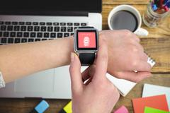 Composite image of woman using smartwatch Stock Photos
