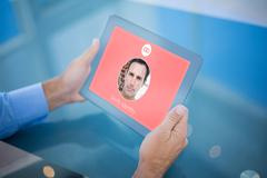 Composite image of businessman using his tablet Stock Photos