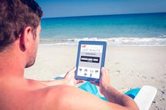 Composite image of man using digital tablet on deck chair at the beach Stock Photos