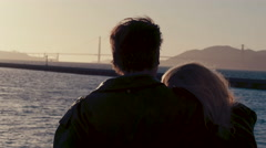 Silhouette of middle-aged couple look out over the San Francisco bay at sunset Stock Footage