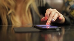 Stock Video Footage of Hand of a woman who moves her fingers over touchscreen smartphone, likely see 1