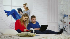 Three young people relaxing with gadgets - stock footage