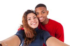 Happy mixed race couple taking a selfie photo over a white background - stock photo