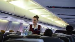 Stewardess at work in flying commercial aircraft cabin - PAN Stock Footage