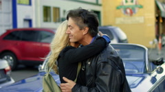 Romantic middle-aged woman hugs and kisses her husband in front of a classic car Stock Footage