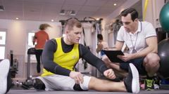4K Man with prosthetic leg working out at the gym with personal trainer - stock footage
