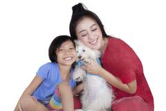 Cute girl and her mother hug maltese dog - stock photo