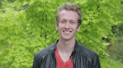 young blond man in leather jacket standing outside and smiling at camera - stock footage
