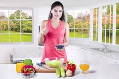 Woman with superfood shows thumb up - stock photo