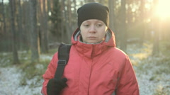 Sad girl walking alone in the winter park. Steadicam shot. - stock footage